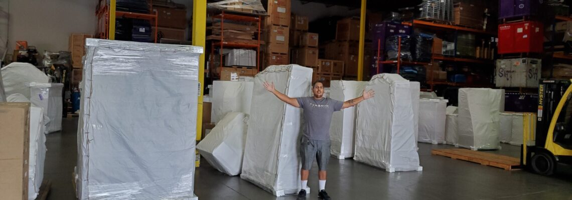 pyramid logistics worker posing happily in a warehouse