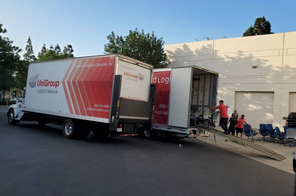 logistics company team loading office equipment into a truck with specialized equipment
