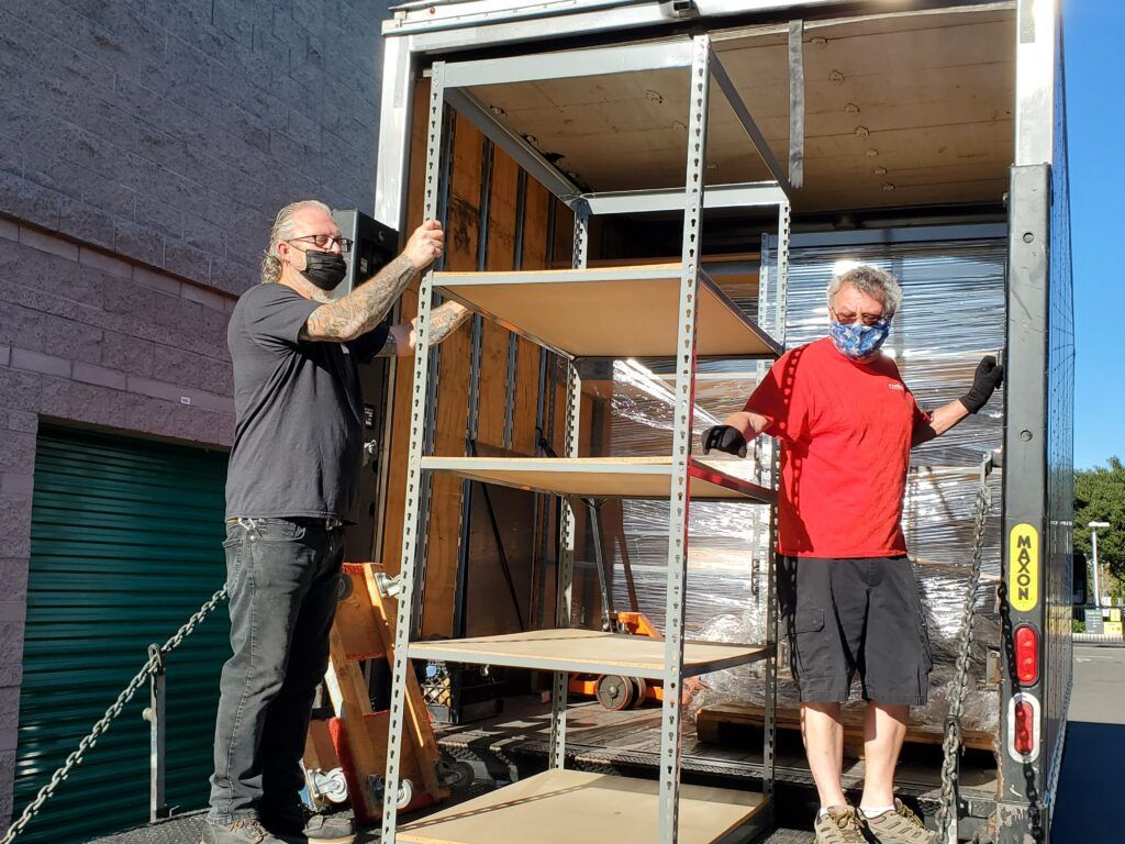 two men with masks on unloading a fixture with care